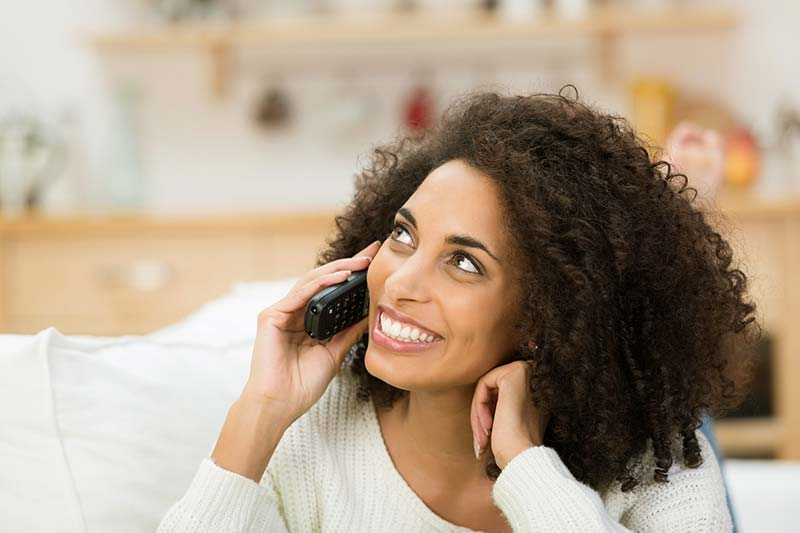 Woman smiling while on the phone with one of our certified home inspectors
